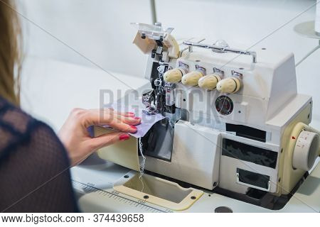 Professional Tailor, Seamstress Using Overlocking Sewing Machine - Close Up Over Shoulder View. Tail