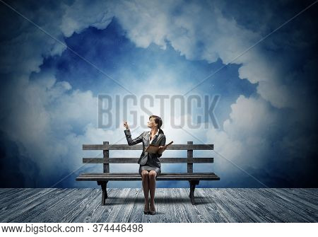 Young Woman Holding Open Book On Wooden Bench Outdoor. Beautiful Girl In Business Suit Finger Pointi
