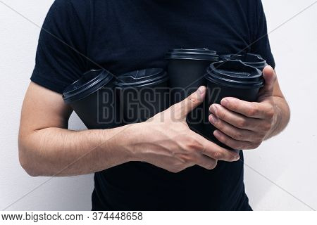 Caucasian Man Holds Black Takeaway Paper Coffee Cups In Hid Hands, No Folder, Face Hidden, Close Up,