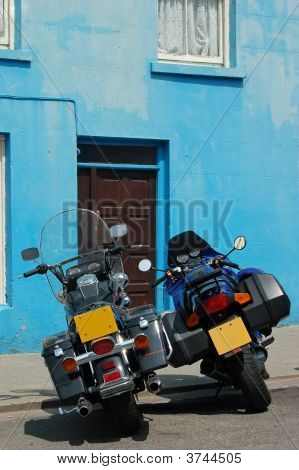 Two Motorbikes Parked Before Blue Plastered Wall