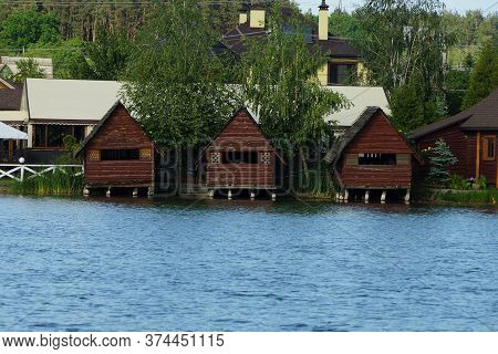A Row Of Three Brown Wooden Arbors Stand On The Lake Water In Green Vegetation