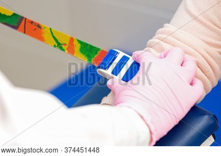 Nurse Hands Are Tightening Harness On Arm To Take Blood, Close Up.