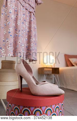 Shoes on top of a colored cardboard box in a bedroom. In the background you can see a bed and a lit lamp.
