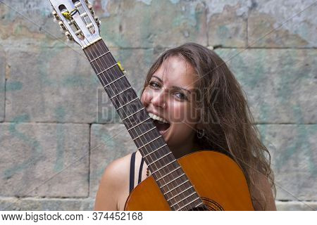 Young Optimistic Curly Hippie Girl Holding And Biting Guitar. Music Concept. Fun Happy Woman With Gu