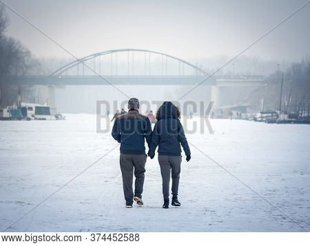 Pancevo, Serbia - January 22, 2017: People, A Couple, Walking On The Frozen Timis Tamis River During