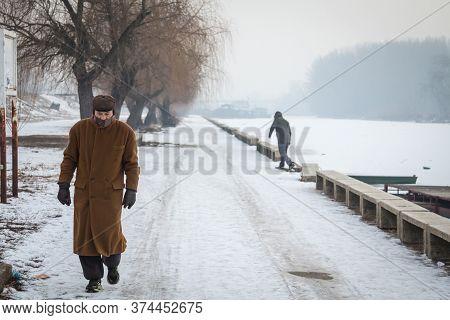 Pancevo, Serbia - January 22, 2017: Old Man, Senior, Walking On The Frozen Timis Tamis River During