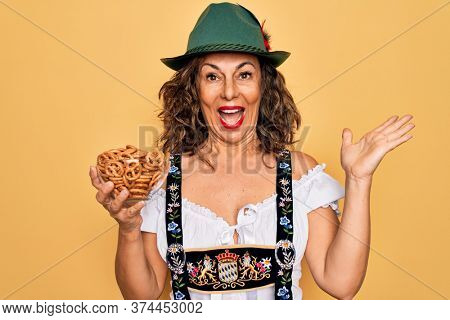 Middle age woman wearing traditional octoberfest dress holding bowl with baked pretzels very happy and excited, winner expression celebrating victory screaming with big smile and raised hands