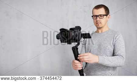 Professional Videographer Shooting Video With Modern Dslr Camera On 3-axis Gimbal Over Grey Concrete