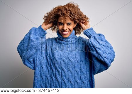 Young beautiful african american woman wearing turtleneck sweater over white background Smiling pulling ears with fingers, funny gesture. Audition problem