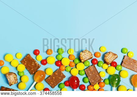 Multi-colored Sweets, Lollipops And Chocolate On A Blue Background. The Concept Of Sweets For Childr