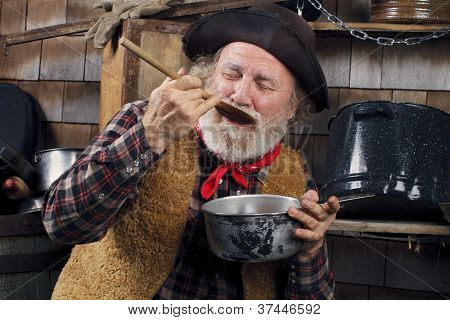 Old Cowboy Cook Tasting Food From Outdoor Kitchen