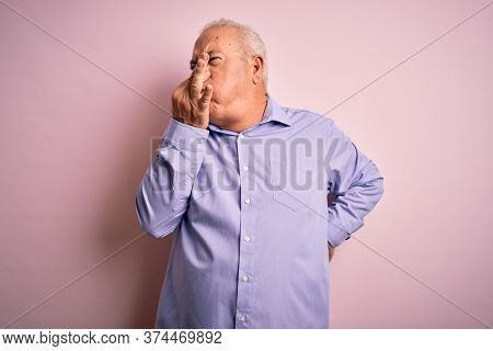 Middle age handsome hoary man wearing casual shirt standing over pink background smelling something stinky and disgusting, intolerable smell, holding breath with fingers on nose. Bad smell