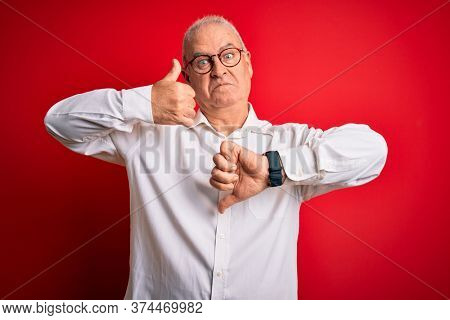 Middle age handsome hoary man wearing casual shirt and glasses over red background Doing thumbs up and down, disagreement and agreement expression. Crazy conflict
