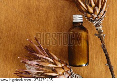 Herbal Organic Ubtan In Glass Bottle On Wooden Background With Dried Protea Flowers, Flat Lay. Ubtan