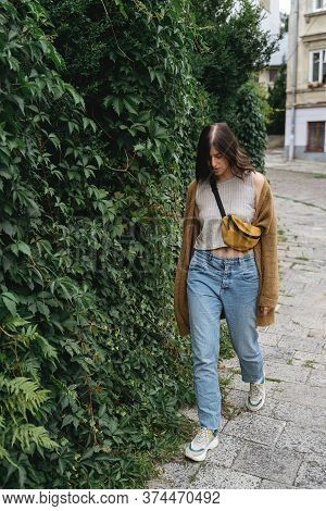 Young Woman In Casual Fashionable Outfit Walking At Green Bush Wall In City Street.stylish Hipster G