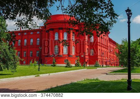 Kiev, Ukraine. 07.05.2012. Kiev University. Bright Red Building Surrounded By Green Trees.