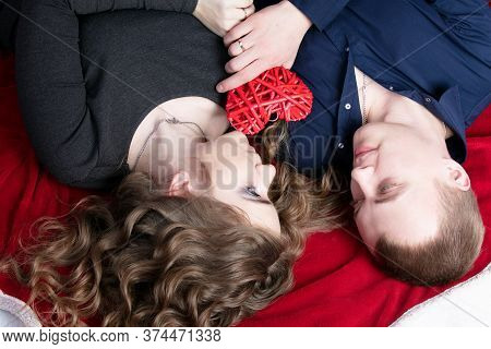 Loving Couple From Top To Bottom. Man And Woman With A Red Heart. Beautiful Young Husband And Wife.c