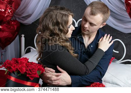 Loving Couple From Top To Bottom. Man And Woman With Red Roses In The Bedroom. Beautiful Young Husba