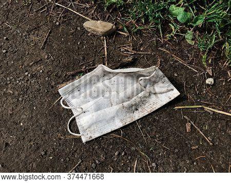Coronavirus Plastic Waste Environmental Pollution. Disposable Dirty Face Mask On Ground, Single Use