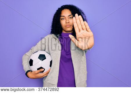 African american curly player woman playing soccer holding football bal over purple background with open hand doing stop sign with serious and confident expression, defense gesture