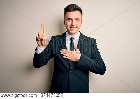 Young handsome business man wearing elegant suit and tie over isolated background smiling swearing with hand on chest and fingers up, making a loyalty promise oath