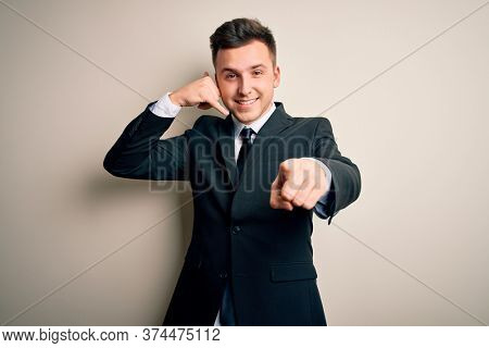 Young handsome business man wearing elegant suit and tie over isolated background smiling doing talking on the telephone gesture and pointing to you. Call me.