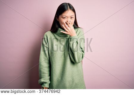 Young beautiful asian woman wearing green winter sweater over pink solated background smelling something stinky and disgusting, intolerable smell, holding breath with fingers on nose. Bad smell