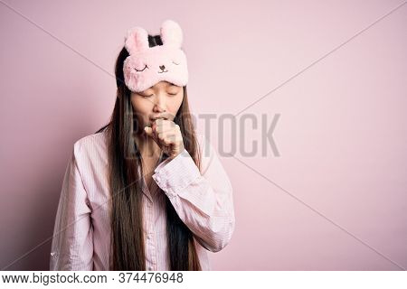 Young asian woman wearing pajama and sleep mask over pink isolated background feeling unwell and coughing as symptom for cold or bronchitis. Health care concept.