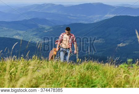 Conquer The Peaks. Man Hiker With Guitar Walking On Top Of Mountain. Guy Hiker Enjoy Pure Nature. Mu