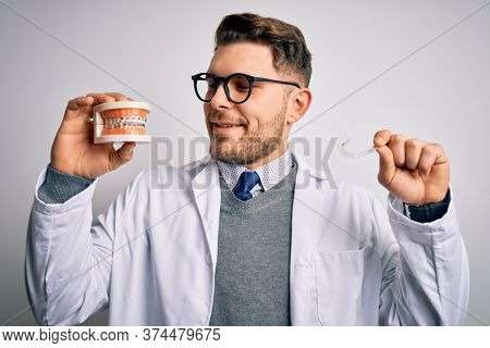 Professional dentist doctor smiling and holding denture with braces and invisible aligner, comparing healthy orthodontics teeth alignment