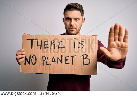 Young activist man holding protest banner for climate change and environment change with open hand doing stop sign with serious and confident expression, defense gesture