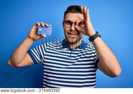 Young man with blue eyes wearing glasses and holding credit card over blue background with happy face smiling doing ok sign with hand on eye looking through fingers