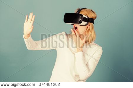 Woman Wearing Virtual Reality Goggles. Person With Virtual Reality Helmet Isolated On Blue Backgroun