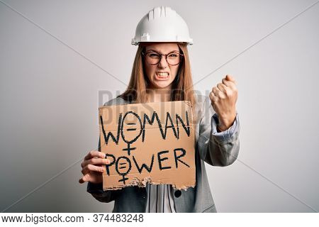 Young redhead architect asking for women rights holding banner with woman power message annoyed and frustrated shouting with anger, crazy and yelling with raised hand, anger concept