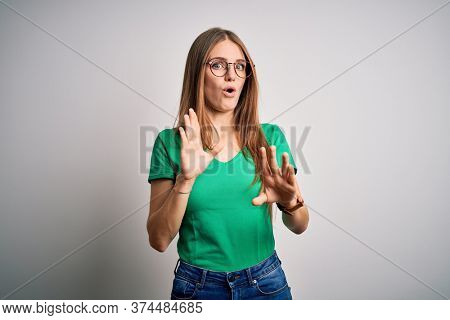 Young beautiful redhead woman wearing casual green t-shirt and glasses over white background Moving away hands palms showing refusal and denial with afraid and disgusting expression. Stop.