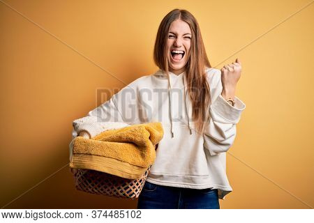 Young beautiful redhead woman doing housework holding wicker basket with clothes screaming proud and celebrating victory and success very excited, cheering emotion