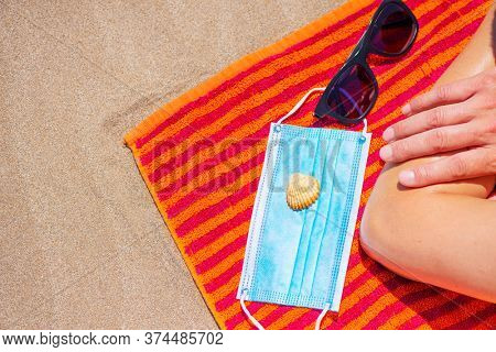high angle view of a caucasian man, lying face down on a colorful orange towel on the beach, next to his sunglasses, a seashell and a blue surgical mask