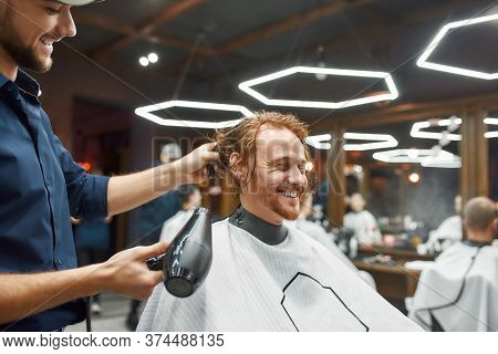 Great Day In Barbershop. Side View Of Young Smiling Redhead Guy Sitting In Barbershop Chair While Ba