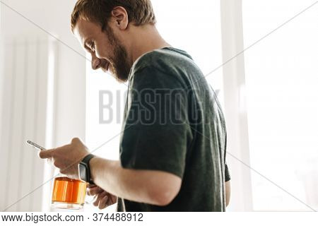 Photo of smiling redhead man with beard drinking tea while using mobile phone in kitchen at home
