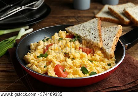 Tasty Scrambled Eggs With Sprouts, Cherry Tomato And Bread In Frying Pan On Table