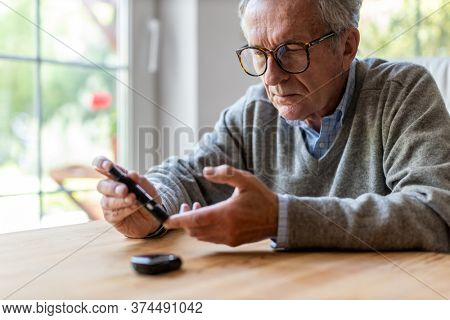 Mature Man Checking Blood Sugar Level With Glucometer