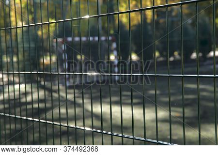 Blurred Image Of A Sports Field Closed To The Public. Lattice Fencing At The Stadium. Close-up, Crop