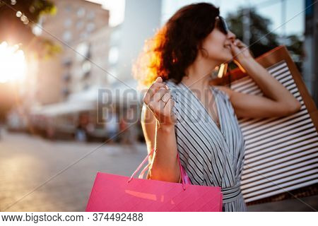 Happy Girl Stands Near Boutique Shop Holding A Few Bags With Purchases. Young Woman Is Glad To Buy N