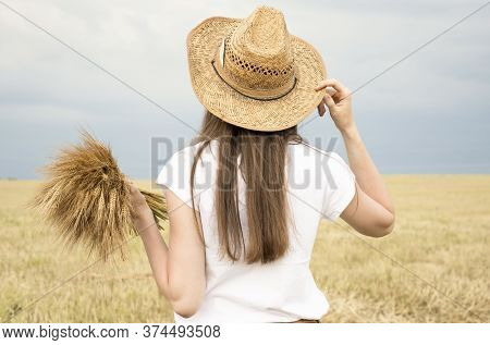 Backview Of Slender Well Shaped Woman Holding Her Arms Up, Having Straw Hat In One Hand, Standing In