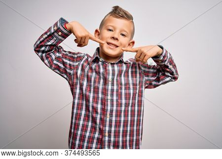 Young little caucasian kid with blue eyes wearing elegant shirt standing over isolated background smiling cheerful showing and pointing with fingers teeth and mouth. Dental health concept.