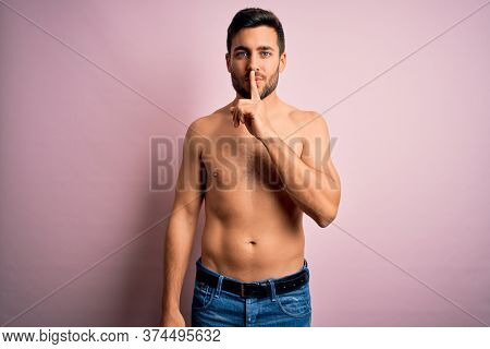 Young handsome strong man with beard shirtless standing over isolated pink background asking to be quiet with finger on lips. Silence and secret concept.