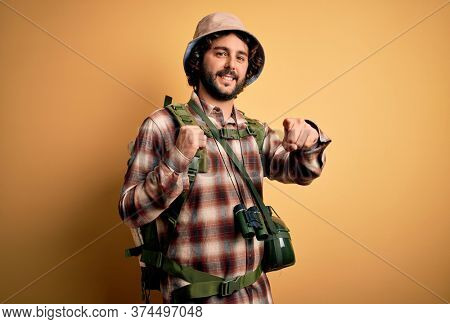 Young hiker man with curly hair and beard hiking wearing backpack and water canteen pointing to you and the camera with fingers, smiling positive and cheerful