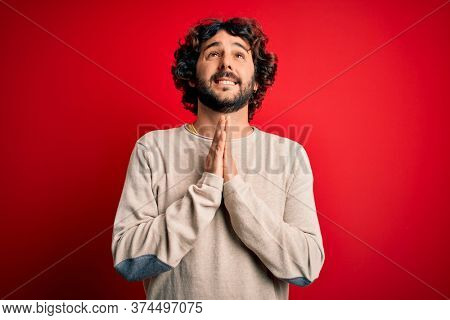 Young handsome man with beard wearing casual sweater standing over red background begging and praying with hands together with hope expression on face very emotional and worried. Begging.
