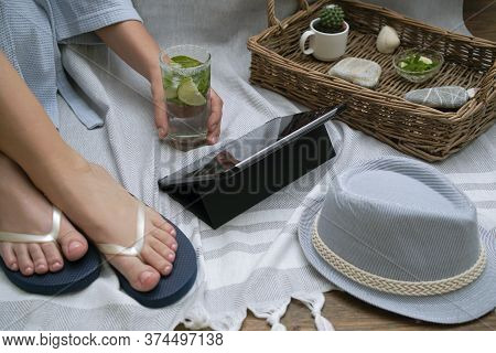 Legs In Flip-flops And A Hand Reaching For A Cold Glass With A Cocktail Of A Woman Who Had A Home Pi
