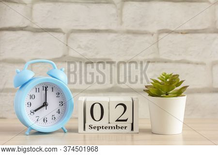 September 2 On A Wooden Calendar Next To The Alarm Clock.september Day, Empty Space For Text.calenda